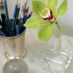 pencils in container and green flower on desk