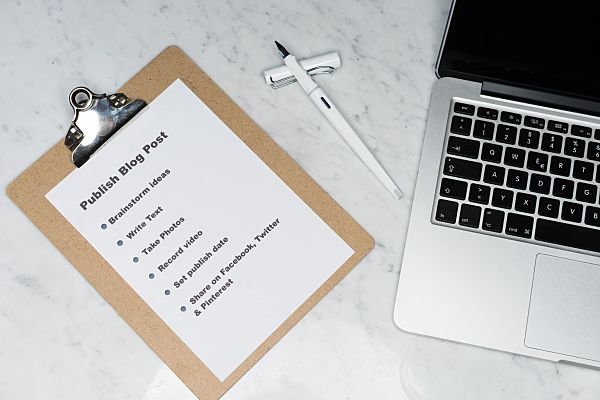notes on a clipboard about writing a blogpost along side a laptop